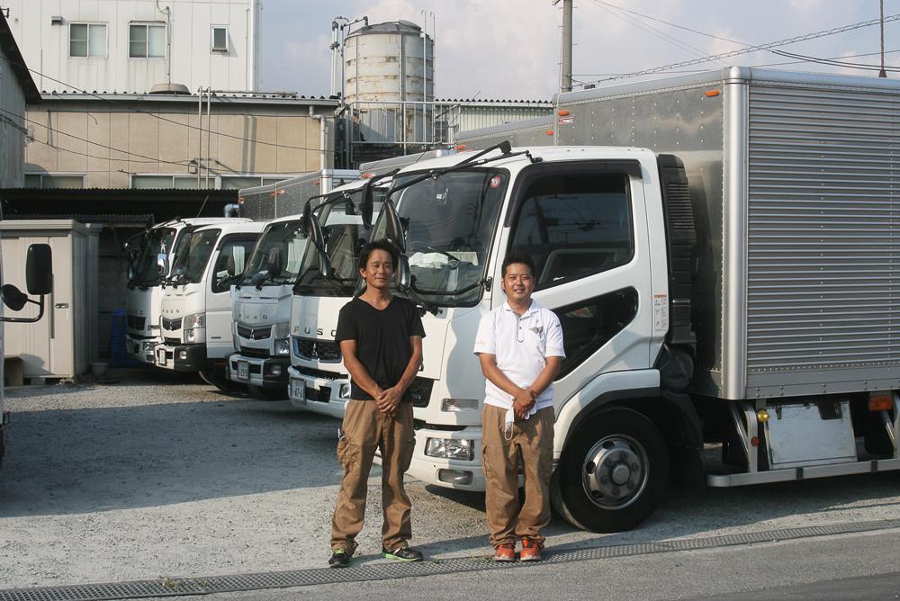 配送トラックをバックに立つ運輸課の社員